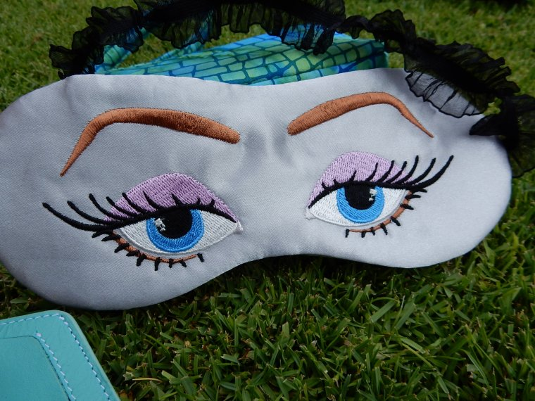 """I never sleep on planes"" eye mask.  Anita Goodesign embroidery.  Gray poly satin fabric, black lace elastic."